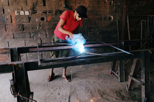 A worker manufactures doors and windows of iron inside a workshop in Benghazi