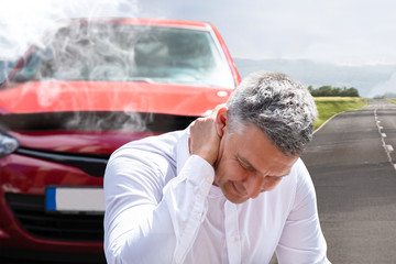 Man Suffering From Neck Pain In Front Of Breakdown Car
