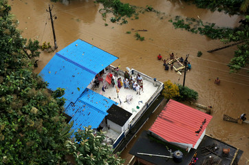 People wait for aid on the roof of their house at a flooded area in the southern state of Kerala