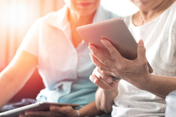 .Happy elderly twin senior people society lifestyle concept. Ageing Asia women using tablet share social media together in wellbeing county home.
