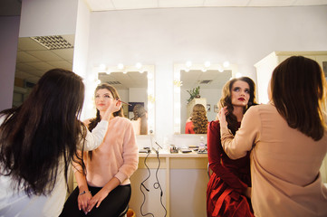 Professional makeup artists working with beautiful young women