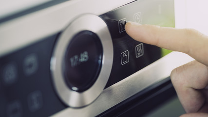 Male finger is touching the button of modern panel of electric oven.