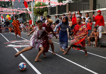 Men dressed in women's clothes play football during a traditional competition to celebrate Indonesia's Independence Day in Jakarta