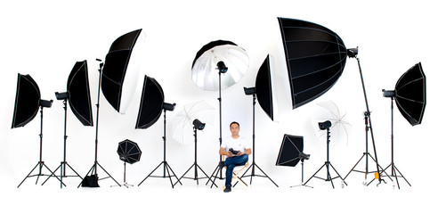 Asian photographers sit on the director's chair with flash studio lights a lot of patterns around on white background.