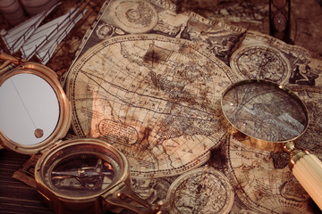 Foto op Plexiglas Wereldkaart Old vintage maps and marine equipment like compass, magnifier or hourglass and ship. Columbus Day concept.