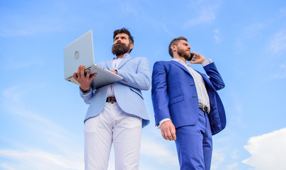 Always in touch. Men well groomed businessman holds laptop partner speak phone blue sky background. Communicating skill. Men formal suits modern technology manager entrepreneur answer phone call