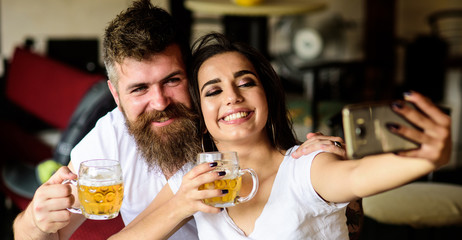 Couple in love on date drinks beer. Best friends or lovers drinking beer in pub. Man bearded hipster and girl with beer glass full of craft beer. Take selfie photo to remember great date in pub