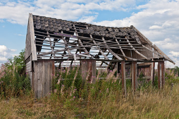 Old decaying barn in the middle of a grassland field with missing walls and holes in the roof on a sunny day with blue sky and clouds