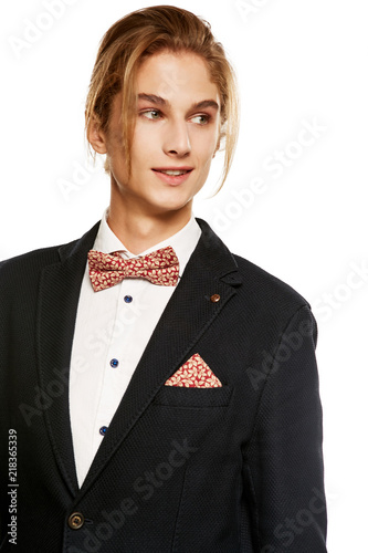 08f32307da A young man in a black suit jacket and button up shirt, accessorized with a  red fleaf pattern bow tie and matching pocket square.