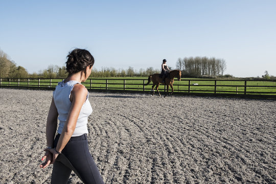 Woman trainer watching a teenage girl riding on a baybrown horse in paddock.