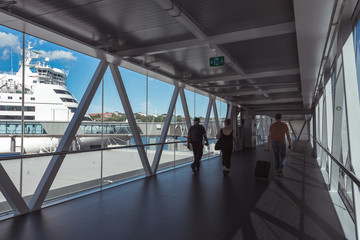 International ship terminal of the largest port in Stockholm. The way to a large tourist liner. Tunnel for tourists and passengers. View of a white ship through panoramic windows.