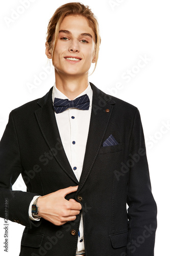 1d134979c3 A handsome young man in a black suit jacket and shirt, accessorized with a  navy blue pinstripe bow tie and pocket square. The blond guy smiling while  ...