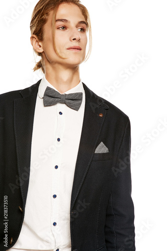 1d90494958 A handsome young man in a black suit jacket and button up shirt,  accessorized with a grey pinstripe bow tie and pocket square. The blond guy with  a ponytail ...