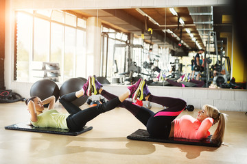 Two determinate young girls doing crunches with legs in the air .