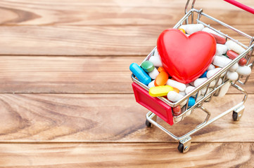 Shopping cart with pills and red heart on wooden background. Space for text. Close up. Medical concept.