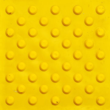 Top view of footpath tiles. Yellow circle buttons pattern. A stop signal for blind person. Solid square background