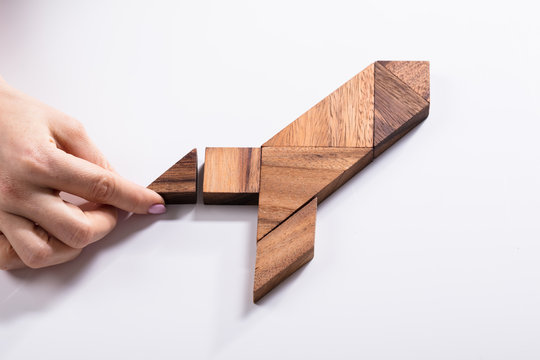 Woman Making Rocket With Wooden Tangram Puzzle
