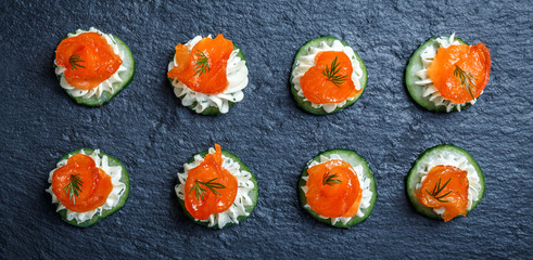 Stores à enrouleur Entree Appetizer canape with salmon, cucumber and cream cheese on stone slate background close up. Delicious snacks, sandwiches, crostini, brushetta, antipasti on party or picnic time. Top view