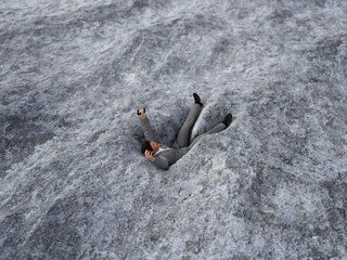 businessman falling in the sand