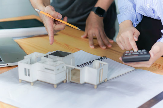 Architect showing new family house model to customer in office working on architects project