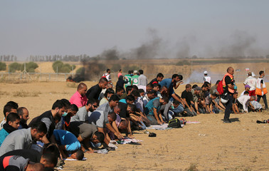 Palestinians pray during a protest demanding the right to return to their homeland at the Israel-Gaza border, in the southern Gaza Strip