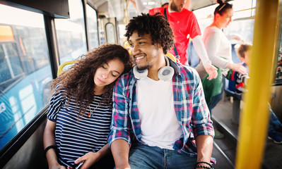Cute curly girl is leaning on her boyfriend in a bus.