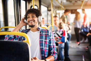 Young Afro-American man is sitting in a bus with headset on his head and listening to the music.