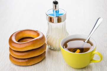 Stack of bread rings, yellow cup of tea, sugar bowl