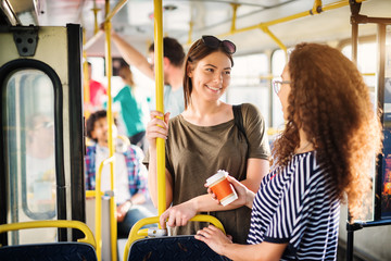 Two beautiful best friends are talking while standing in a bus full of people.
