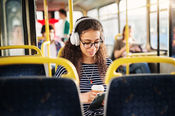Beautiful girl with curly hair is sitting alone in a bus a listening to the music.