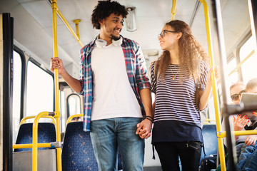 Young beautiful couple looking at each other while leaving the bus.