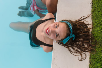 Overhead view of a young blond girl smiling at camera on the edge of a swimming pool