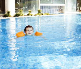 little cute boy in swimming pool wearing orange handcarves