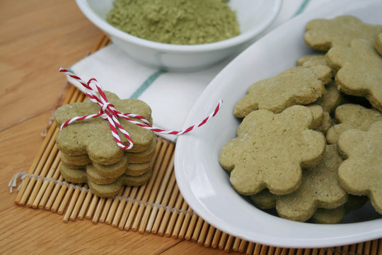 Homemade Green Matcha tea cookies in shape of flower on wooden table