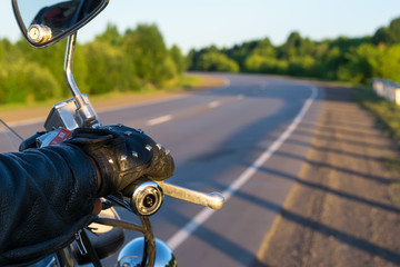 closeup of the hand of the biker on the control handle of the motorcycle and the view of the road