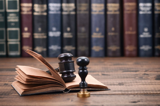 Notary Seal, Judge Gavel and Law book on a wooden background.