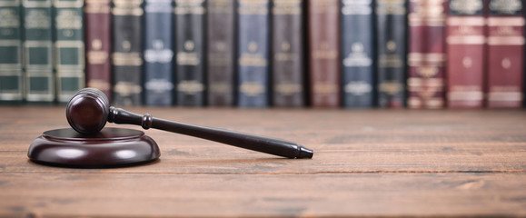 Judge Gavel and Law books on a  wooden background.