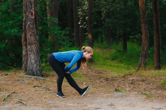 Girl in blue sportswear doing exercises outdoors in coniferous forest. Humstring stretch bending forward to warm up. Healthy lifestyle sport concept.