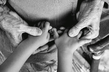 an elderly woman holding children's hands, a wooden cane on the street. great-grandmother and great-grandson. black and white photo