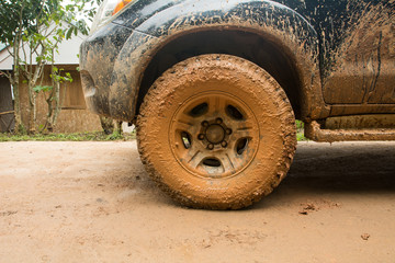 Closeup dirty Wheels in a countryside, Adventure background. Detail of dirty off-road car, Dirty offroad car side