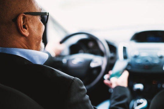 Mature businessman is using his phone while driving a car.