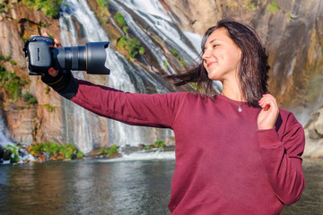 beautiful girl makes selfie with SLR camera