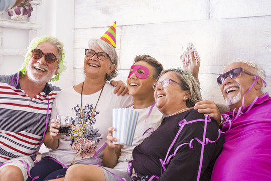 group of cheerful happy caucasian people mixed ages generations from grandfathers to grandson having fun together celebrating a party like brithday. carnival concept at home for family - laughing