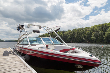 A wakeboard boat at a wooden dock in the Muskokas on a sunny day. Wall mural