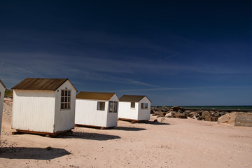 Small white holiday beach houses on the sand is typical for the northern danish coastline. Danish Beach, in Lokken and Lønstrup in North Jutland in Denmark, Skagerrak, North Sea