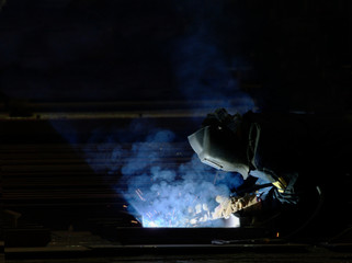 Worker welding production at an industrial plant in the smoke. side view