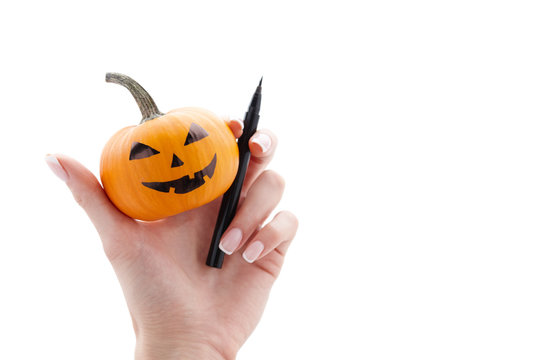 Woman's hand holding small painted halloween pumpkin and black marker pen isolated on white background. Holiday decoration concept.