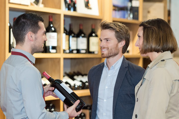 couple choosing wine with sales assistant in wine shop