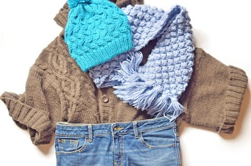 Fall and winter fashion/ Flat lay photo winter outfit. Brown woolen sweater, blue jeans, knitted scarf and hat
