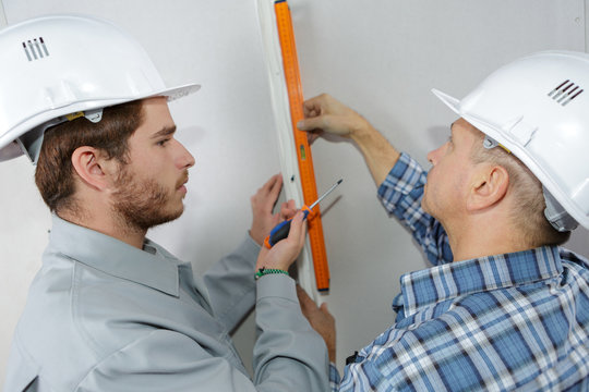 apprentice construction worker leanring with experienced tradesman